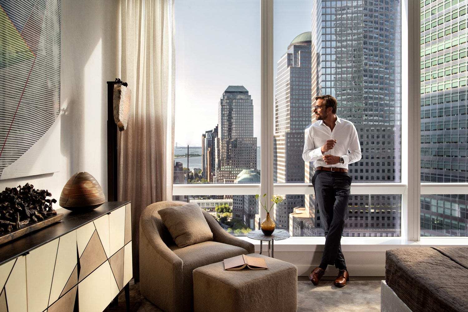 man in bedroom, luxury condominium overlooking downtown New York