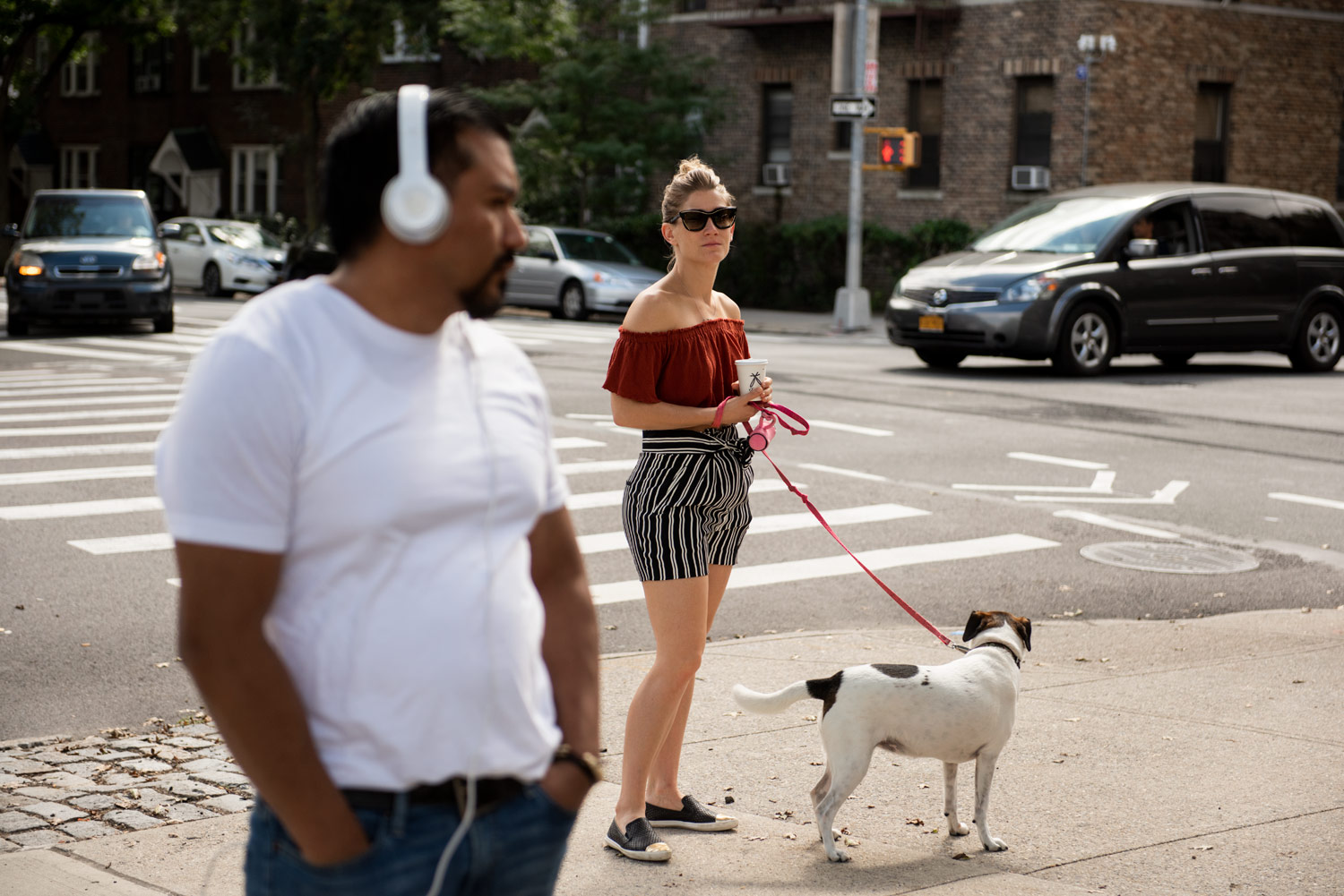 street scene, woman with dog, man wearing headphones