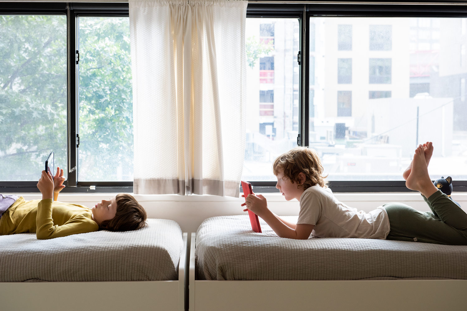 children with iPads on their beds